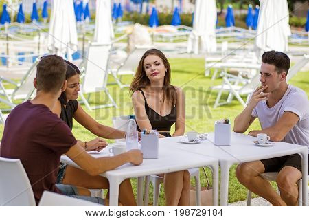 Young handsome men and attractive women sitting at white plastic table drinking smoking talking.