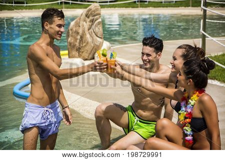 Young brunette men and women relaxing at pool smiling clinking with glasses tanning.