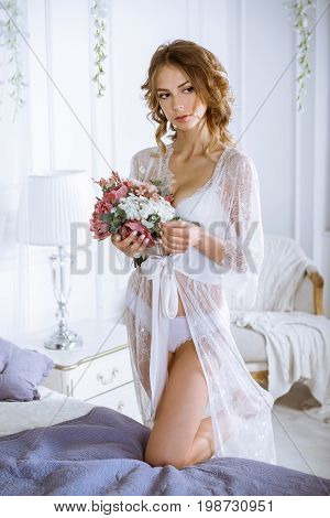 Beautiful sexy lady in elegant white robe. Close up fashion portrait of model indoors. Beauty brunette woman and bouquet. Attractive female body in lace lingerie. Closeup girl in underwear and flowers