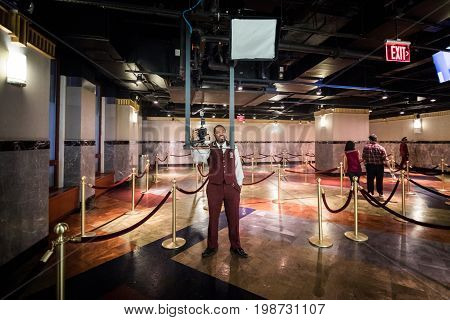 Employee Taking Tourists In Pictures On Arrival Inside The Empire State Building.