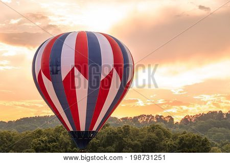 Hot air balloon in red, white and blue floats among the mountains in a beautiful sky at dusk