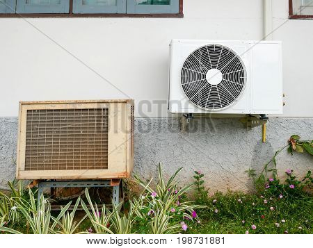 new air conditioner condenser and old air conditioner condenser unit standing outdoors on wall