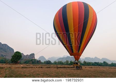VANG VIENG LAOS - MARCH 15 2017: Horizontal picture of a striped balloon landing in Vang Vieng Laos.