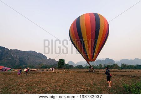 VANG VIENG LAOS - MARCH 15 2017: Panorama picture of a striped balloon landing in Vang Vieng Laos.
