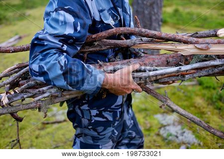 The man is carrying an armful of brushwood in his hands. Preparations for kindling a fire.