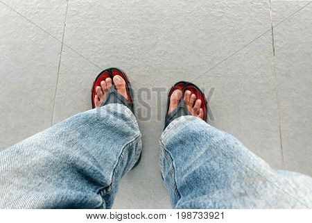 Man's feet top view wearing jeans and sandals.