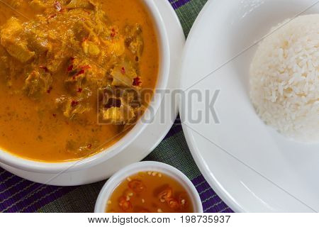 Khmer curry with chicken with a rice and chili sauce at