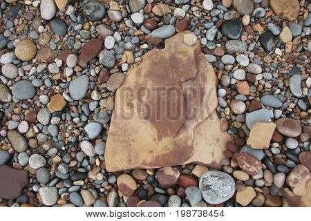 A large sandstone rock with pebbles around it.  Pictured Rocks National Lakeshore, Upper Peninsula, Michigan