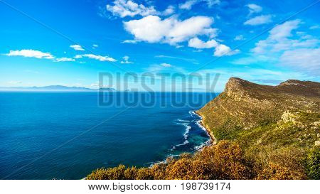 The rugged coast and wind swept peaks near Cape Point on the Cape Peninsula in South Africa with Cape Agulhus, the most southerly point of the African Continent in the distant