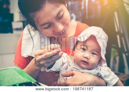 Lovely asian baby girl sitting on mother lap. Happily mom smiling and take care to comfort her daughter with love at home. Happy family spending time together. Vintage tone. Mother's Day celebration.