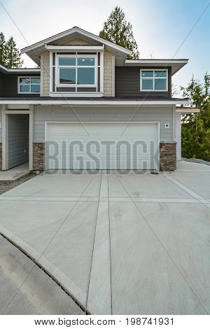 Concrete driveway of brand new residential triplex house on the final stage of construction. Family house for sale