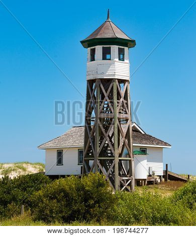 COROLLA, NORTH CAROLINA - JULY 14, 2017:  Wash Woods lookout tower and boathouse at the Old Coast Guard Station, built by the United States Coast Guard in 1917.