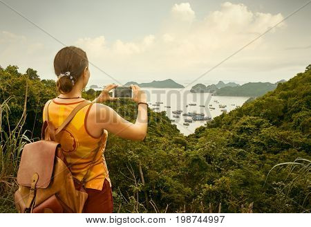 hiker with backpack enjoying on view photographing the bay of Cat Ba.Vietnam Mountains and sea landscape travel to Asia happiness emotion summer holiday concept
