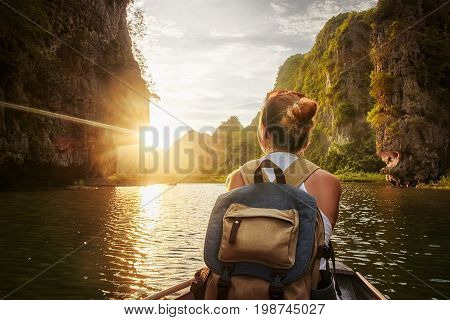 Happy woman with backpack traveling by boat enjoying sunset among of karst mountains in the North of Vietnam. Travel and active lifestyle summer holiday concept.