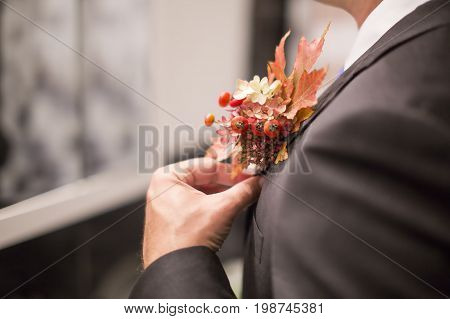 Groom attach flowers to the suit. man's hand adjusts the wedding boutonniere. Wedding boutonniere on a black tuxedo