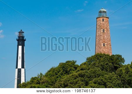 VIRGINIA BEACH, VIRGINIA - JULY 11, 2017:  The old Cape Henry lighthouse built of brick in 1792 and the newer from cast-iron plates in 1881; both are located on the Fort Story military base.