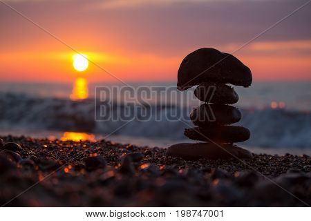 Silhouette of a rock cairn stacked on the beach of Lake Superior at sunset.