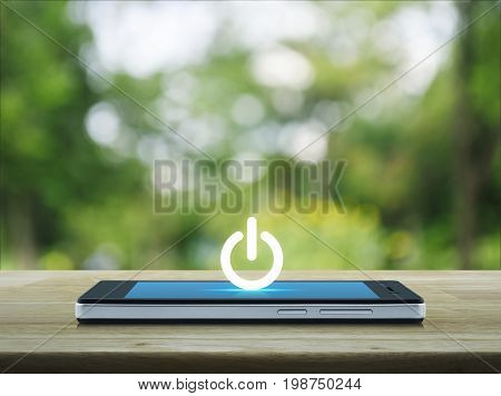 Power button icon on modern smart phone screen on wooden table over blur green tree in park Start up business concept