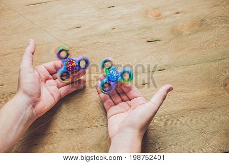 A Man Hand Holding Hand Spinner Or Fidget Spinner Over Wooden Background