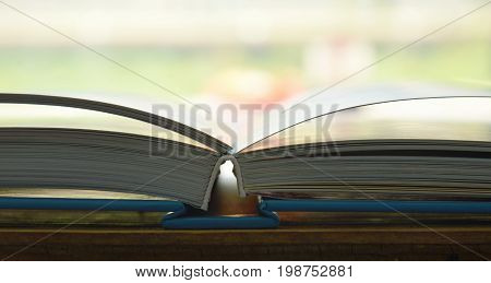 book with hard cover opened on wooden board
