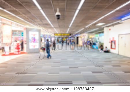 people walking around duty free shop in airport terminal - blur for background