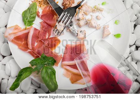 A view from above a white plate with remains of delicious food on a white stones background. The prosciutto or ham, walnuts, basil and cheese on a plate. Left-over food.