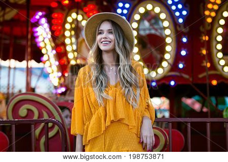 Beautiful smiling tourist woman having fun at amusement park at hot summer day trip.