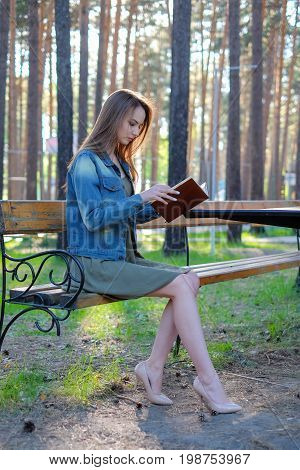 beautiful girl reading a book outdoor in the park