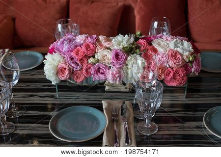 Table served with flowers and dishware for event in modern restaurant close up