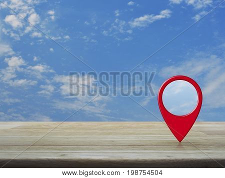 Map pin location button on wooden table over blue sky with white clouds Map pointer navigation concept