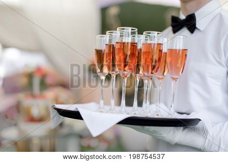 Faceless man in uniform holding tray with filled champagne glasses while serving on event.