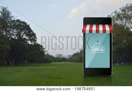 Modern smart mobile phone with online shopping store graphic and open sign on green grass field in city park Shop online concept