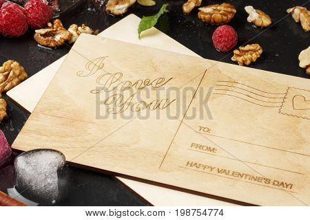 Close-up of a beautiful composition of romantic postcards, fruity hearts, and walnuts on a black wooden background. Pink raspberries and ice hearts next to a love note. Romance concept.