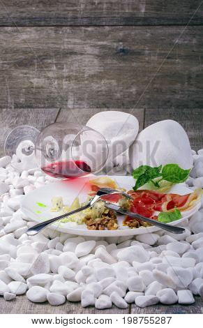 A beautiful composition of a delicatessen plate and a wineglass on white stones. A ceramic round plate with delicious snacks and a glass of semisweet red wine on a gray wooden background. Copy space.