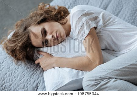 Bad day. Cheerless unhappy young woman resting on the pillow and thinking about her problems while having a bad day