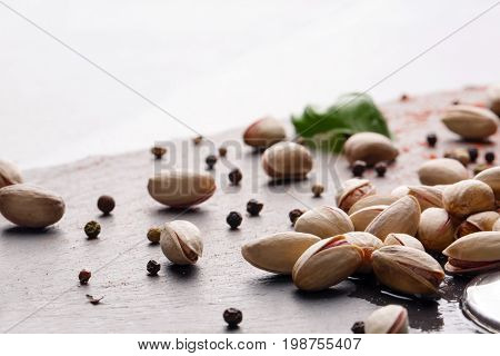 Close-up of beautiful salty cracked pistachios, green basil leaves, and black pepper on a light wooden table. Tasty appetizers for alcoholic beverages isolated on a white background. Copy space.