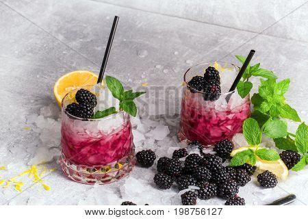 Couple of fancy glasses full of cold, icy beverage with spicy mint, lemon pieces, juicy blackberries and black straws on a frozen white table background. Refreshing cocktails with fruits and berries.