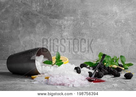 A metal bucket full of crushed ice on a gray table background. A long spoon with sweet berry jam and fresh, cold blackberries. Ice with mint leaves and a cut lemon. Refreshing summer ingredients.