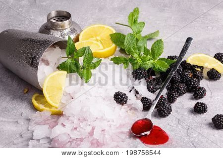 A small metal bucket full of crushed ice on a light table background. A long spoon with sweet berry syrup and fresh cold blackberries. Ice with mint and a cut lemons. Summer cocktail ingredients.