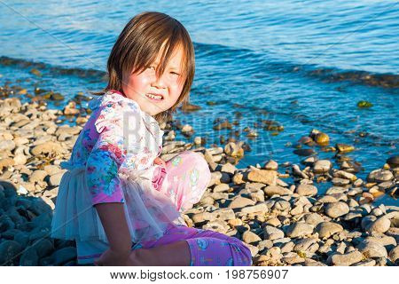 Lake Hovsgol, Mongolia - July 31, 2017: mongolian child plays on the shore of the lake on a sunny summer day