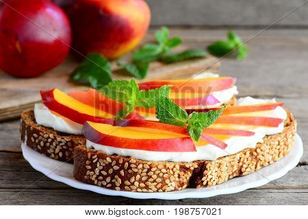 Fruits and cream cheese sandwiches on a plate and old wooden table. Rye bread sandwiches with ripe nectarines, soft cheese cream and mint. Closeup