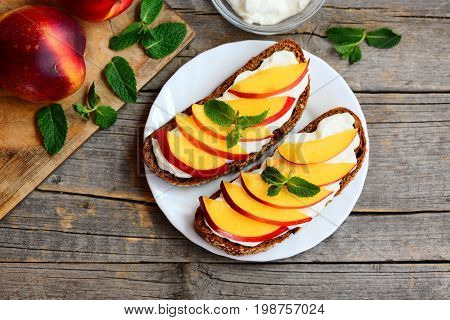 Nectarine cream cheese sandwiches on a plate and vintage wooden table. Rye bread sandwiches with fresh nectarines and soft cheese cream. Top view