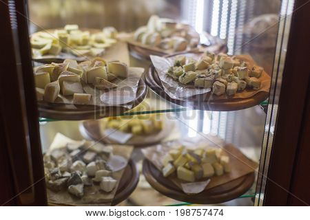 Wooden plates with served assorted cheese cut in pieces standing in restaurant glass fridge.