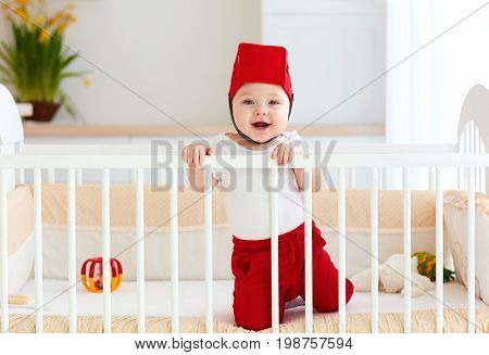 Funny Happy Baby With Toy Basket As Helmet Are In His Cot