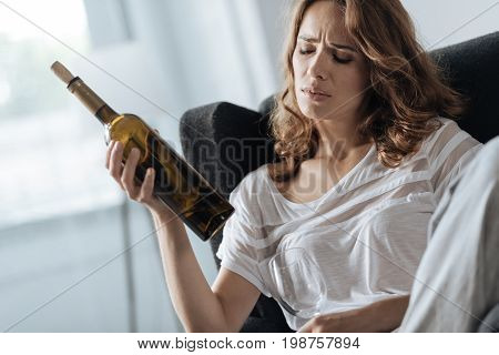 White wine. Upset gloomy cheerless woman sitting in the armchair and drinking white wine while trying to fight her depression