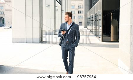 Young urban businessman professional on smartphone walking in street using mobile phone