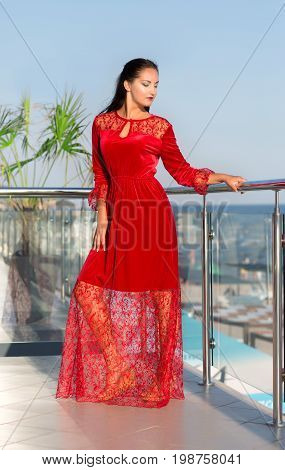 A beautiful young woman in a red dress posing on a light blue sky background. An elegant lady in a saturated scarlet velvet and guipure dress. A gorgeous lady on a hotel terrace.