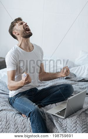 Lack of control over emotions. Furious angry young man holding crumpled paper and looking at the ceiling while sitting in front of his laptop