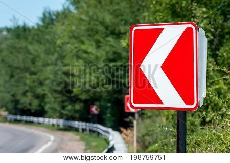 Sign of the left turn. Road signs warn of a sharp turn left.