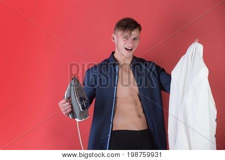 Happy man smiling with iron and white jacket in hands. Macho with muscular torso in open blue shirt on red background. Housework and ironing concept